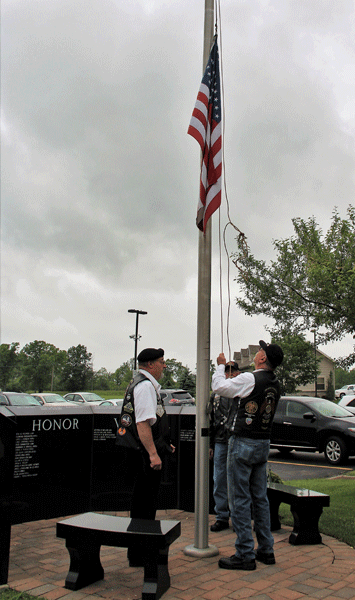 Members of the American Legion Riders Post 1451, raise the flag in front of the Service Persons Memorial at Niagara Hospice.