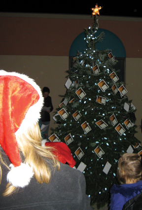 Onlookers enjoy the view of the just illuminated tree in the courtyard at Hospice at Jeanne's House.
