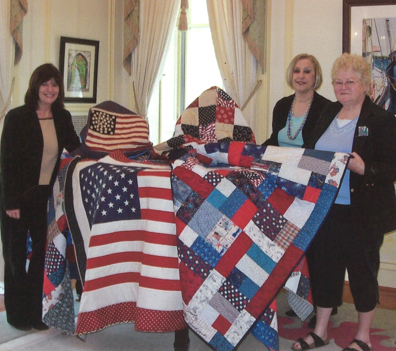 Niagara Hospice Volunteer Services Director, Alice Beck, (left) accepts handmade veteran quilt donations from Kenan House Director Susan Przybyl and Gretchen Lang (right) of the Kenan Quilters.