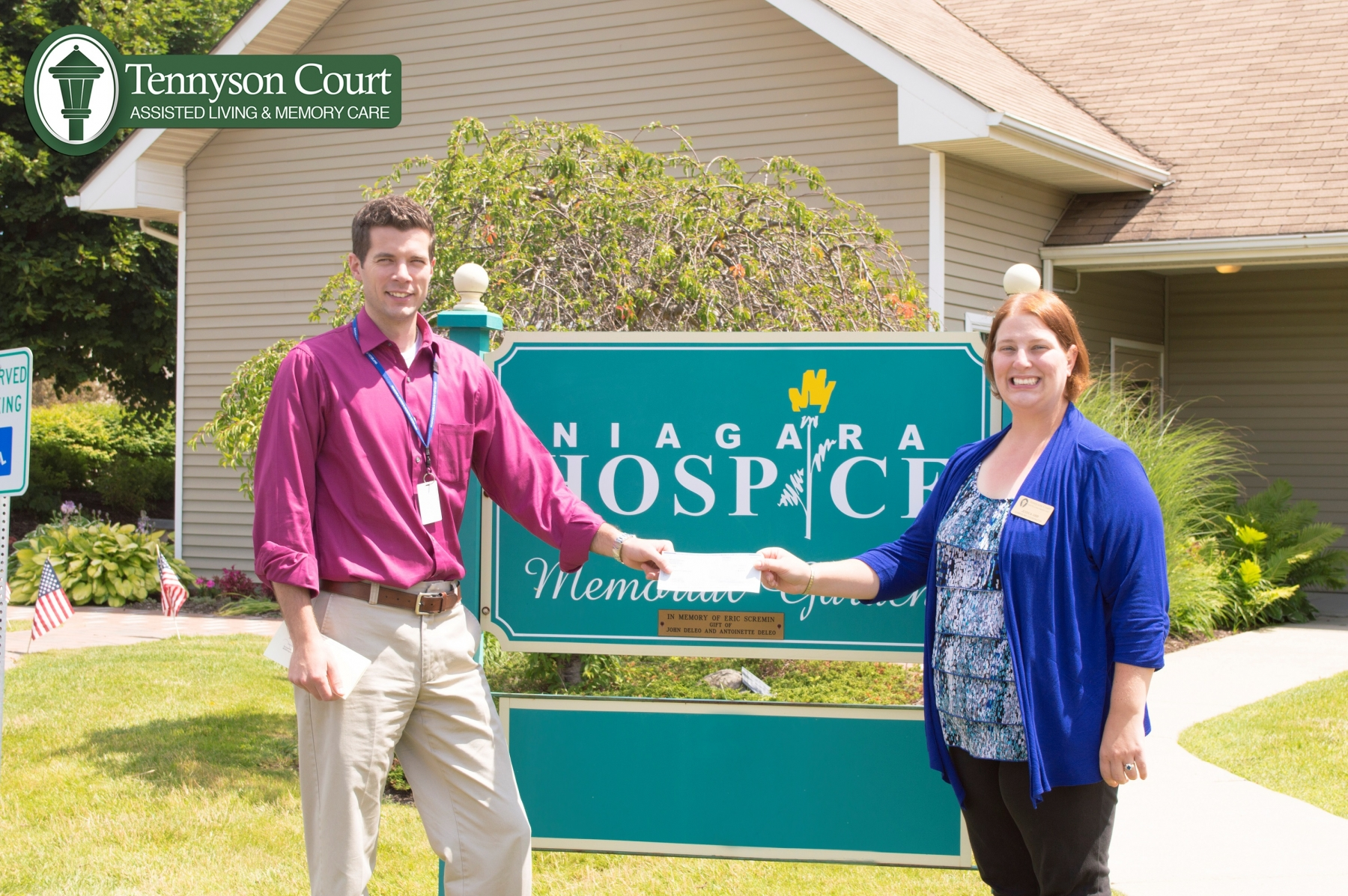 Niagara Hospice Director of Development Brendan McIntyre receives a donation from Tennyson Court Marketing Director Jessica Gibb at Niagara Hospice's campus in Lockport, NY.