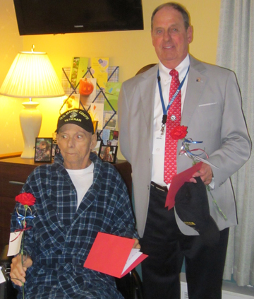 Hospice at Jeanne's House resident and US Marine Corps veteran James Oliverio receives a Veteran's Day card and carnation from Niagara Hospice volunteer and US Air Force veteran James Hildreth this past Veteran's Day.