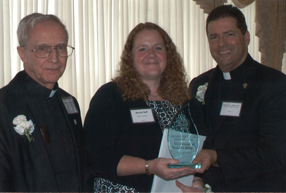 Niagara Hospice volunteer coordinator, Mandy Raff, accepts the Good Neighbor Award on behalf of the Niagara Hospice volunteers from Rev. William O'Brien, CM (left) and Rev. James Maher, CM (right).