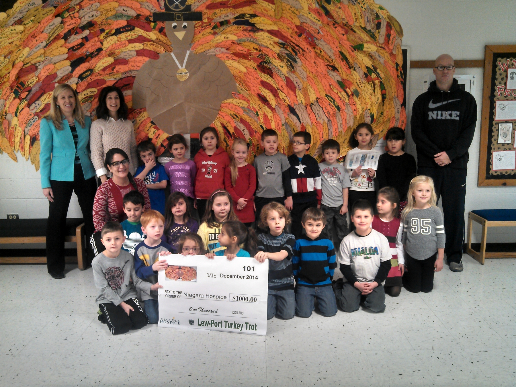 Lewiston Porter Primary Education Center Principal Tamara Larson, along with Physical Education teachers Cindy Sanoian and Matt Bradshaw present Maureen Rizzo of Niagara Hospice with a check for $1000 raised by the Lew-Port Turkey Trot. Students from Mrs. Milleville and Mrs. Allen-Thomas' classes  are shown in front of the turkey that displays feathers sold for a dollar each as part of the event.